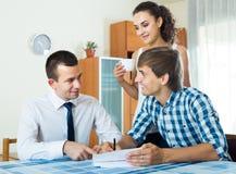 Уверенно продавец и молодые супруги обсуждая контракт Стоковое Фото