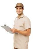 Уверенно работник доставляющее покупки на дом держа доску сзажимом для бумаги стоковые фото