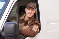 Уверенно работник доставляющий покупки на дом усмехаясь в тележке Стоковые Фото