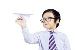 Уверенно ребенк дела держа бумажный изолированный самолет - Стоковые Фото
