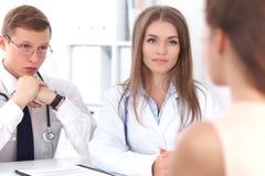 2 уверенно дружелюбных доктора сидя на таблице и слушают к терпеливой истории ` s Медицинский и здравоохранение Стоковые Изображения