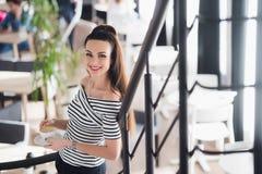 Уверенно руководитель группы Уверенно молодая женщина держа чашку горячего кофе в ее руках и смотря камеру с улыбкой Стоковые Изображения