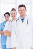Уверенно счастливая группа в составе доктора на медицинском офисе Стоковое Фото