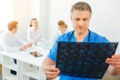 Уверенно тысячелетний радиолог смотря развертку луча x пациента Стоковое Фото