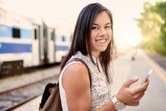 Уверенно тысячелетний студент на идти проверяя ее умный телефон на платформе поезда Стоковые Изображения RF
