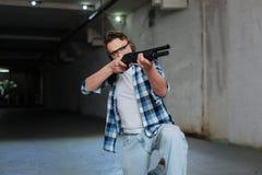 Уверенно умелый стрелок сидя на одном колене Стоковые Фото