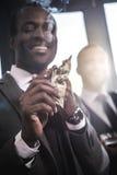 Уверенно усмехаясь сигара освещения бизнесмена с банкнотой доллара Стоковая Фотография RF