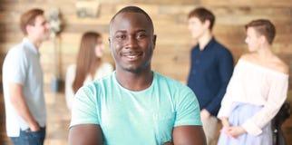 Уверенно успешный черный бизнесмен перед группой людей стоковое изображение rf