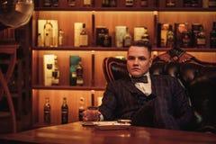 Уверенно человек высшего класса с стеклом напитка в клубе ` s джентльмена Стоковые Изображения