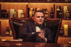 Уверенно человек высшего класса с стеклом напитка в клубе ` s джентльмена Стоковая Фотография