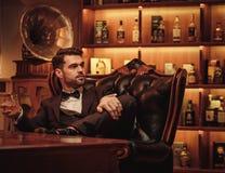 Уверенно человек высшего класса с стеклом напитка в клубе ` s джентльмена Стоковое Фото