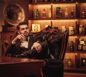 Уверенно человек высшего класса с стеклом напитка в клубе ` s джентльмена Стоковая Фотография RF