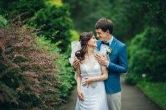 Уверенно элегантный groom и красивая застенчивая невеста держа ou рук Стоковое фото RF