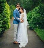 Уверенно элегантный groom и красивая застенчивая невеста держа ou рук Стоковая Фотография RF