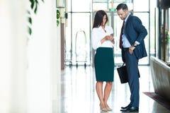 Уверенные деловые партнеры идя в офисное здание и обсуждая работу стоковая фотография rf