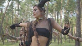 Уверенные женские танцоры с макияжем и в мистических фантастических костюмах танцуя шпунтовой танец в природе Феи леса сток-видео