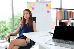 Уверенные молодые азиатские исполнительные усаживание женщины и идея иметь в рабочем месте офиса стоковое изображение rf