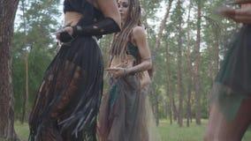 Уверенные танцоры женщин с макияжем и в мистических фантастических костюмах танцуя шпунтовой танец в природе Феи леса акции видеоматериалы