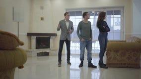 Уверенный агент недвижимости показывает молодой успешной женатой паре новый дом Счастливый человек и женщина смотря вокруг видеоматериал