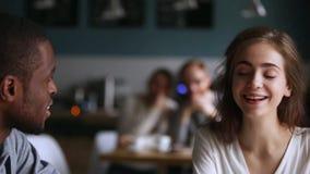 Уверенный африканский человек получая знакомый с кавказской женщиной в кафе акции видеоматериалы