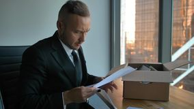 Уверенный бизнесмен в официальном костюме с двигая коробкой в офисе распаковывая детали сток-видео
