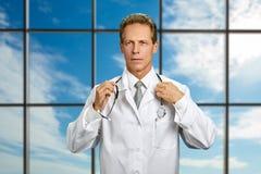 Уверенный доктор регулируя его стетоскоп стоковое изображение