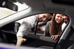 Уверенный молодой продавец объясняя особенности автомобиля молодым привлекательным владельцам стоковая фотография