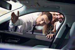 Уверенный молодой продавец объясняя особенности автомобиля молодым привлекательным владельцам стоковые изображения