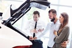 Уверенный молодой продавец объясняя особенности автомобиля молодым привлекательным владельцам стоковое фото