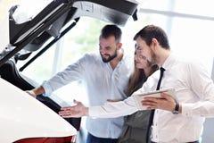 Уверенный молодой продавец объясняя особенности автомобиля молодым привлекательным владельцам стоковые фотографии rf