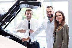 Уверенный молодой продавец объясняя особенности автомобиля молодым привлекательным владельцам стоковое изображение rf