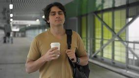 Уверенный молодой человек идя с кофе для того чтобы пойти сток-видео