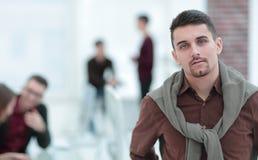Уверенный молодой человек на заднем плане офиса стоковое изображение rf