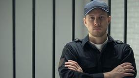 Уверенный охранник тюрьмы смотря к положению камеры около клетки, профессии видеоматериал