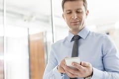 Уверенный профессионал используя мобильный телефон в офисе стоковая фотография