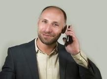 Уверенный успешный бизнесмен говоря на мобильном телефоне имея деловую беседу с усмехаться мобильного телефона жизнерадостный в к стоковая фотография