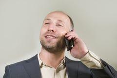 Уверенный успешный бизнесмен говоря на мобильном телефоне имея деловую беседу с усмехаться мобильного телефона жизнерадостный в к стоковые изображения rf