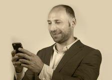 Уверенный успешный бизнесмен используя мобильный телефон имея делать онлайн дело с усмехаться мобильного телефона жизнерадостный  стоковое изображение rf