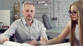 Уверенный человек работая на новом проекте с его ассистентом сток-видео