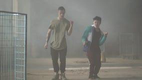2 уверенных молодые люди танцуя в темной и пылевоздушной комнате получившегося отказ здания Парни делая движения и представления  акции видеоматериалы
