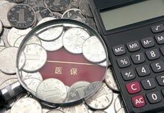 Увеличитель и калькулятор с юанями фарфора на предпосылке банковской книжки медицинского страхования Стоковое фото RF