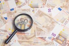 Увеличитель над 50 примечаниями евро стоковые фото