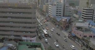 Увиденная занятая дорога с проходить автомобили, шины, мотоциклистов и идя людей, towering небоскребы, здания сток-видео