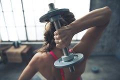 Увиденный от гантели задней женщины фитнеса поднимаясь Стоковые Изображения RF
