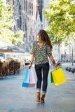 Увиденный от задней женщины с хозяйственными сумками идя на улицу Стоковая Фотография