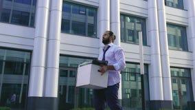 Уволенный красивый человек с бородой, менеджер в официальной одежде, осадил после быть увольнятьым, идет вместе с коробкой  видеоматериал