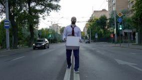 Уволенный красивый человек с бородой, менеджер в официальной одежде, осадил после быть увольнятьым, идет вместе с коробкой  сток-видео