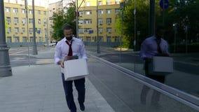 Уволенный красивый человек с бородой, менеджер в официальной одежде, осадил после быть увольнятьым, идет вместе с коробкой  акции видеоматериалы