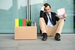 Увольнянный бизнесмен читая извещение прекращения работы стоковые изображения rf