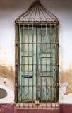 Увяданная зеленая дверь с padlock за решеткой металла на запятнанном whit Стоковые Фото